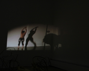 A photograph of a video projected onto a wall. The room is dark, there is an object in the foreground that is illegible