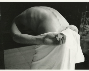 Black and white photograph of a man seen from behind bent over and holding a towel around his waist