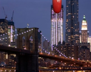 An image of the New York City Skyline from Brooklyn looking at the Brooklyn Bridge toward Manhattan, with a red fingernail at the top of one building
