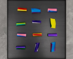 An overview photograph of pieces of colored papers on a black background