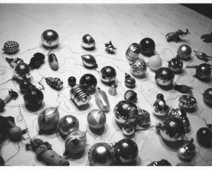 A black and white photograph of christmas ornaments, laid out upon a surface.