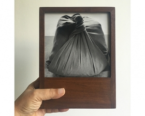 A hand holds a teak wood frame with a black and white photograph of a pothi, a knotted package made of fabric.