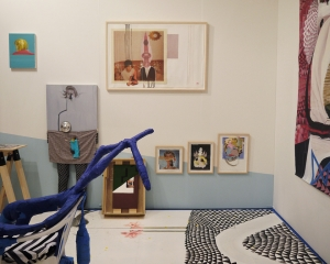 An installation photograph of a portion of Callicoon Fine Art's booth. There are 4 framed collages, a complex floor painted with small black triangles, and a blue sculpture attached to a chair. There are also two paintings near the left edge of the image that are figurative.