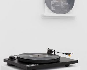 """A photograph of A.K. Burns' record """"Leave No Trace"""" installed on the wall in the background, and on a record player upon a pedestal in the foreground."""