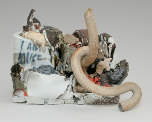 """A sculpture of mixed stoneware. There are several serpentine tube shapes, silver lusters and seemingly molten elements that appear to drip over. At left is a shape that resembles a paint can with the works """"I AM MIKE"""" written upon it."""