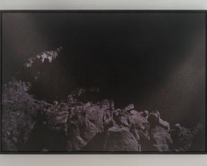 A photograph of a mountainous landscape in purple tones