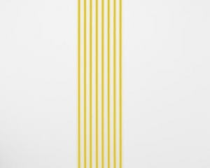 An installation of white gummed paper tape, 8 strips, floor to ceiling, that have a strand of yellow ribbon within each strip.
