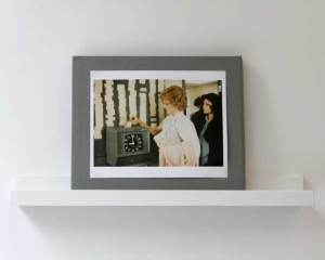 A photograph of a photograph of a woman punching a time-clock, framed in gray