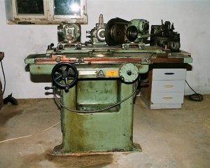 A photograph of a grinder from a factory, seafoam green with oil stains on it, sitting in a desolate room with gray walls and one window