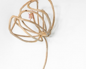 A wooden flower hung on the wall, outlined like a silhouette