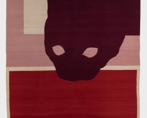 A vertically-oriented textile work with a silhouette of a cat peaking into the center from the top-right corner. The bottom half of the rug is crimson, with a beige border. The upper half is beige with a thick pink border on the left and bottom of the rectangle.