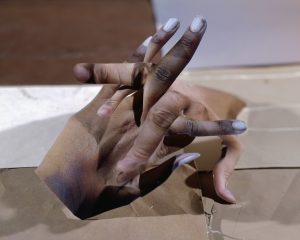 An image of fingers intermingled on a brown paper surface, made out of various collaged papers