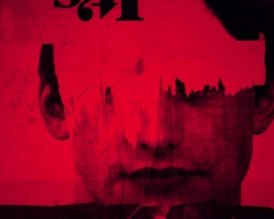 An image of red and black the depicts a male face, with graffiti and portions ripped away.