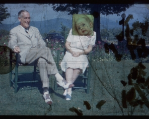 A film still, an elderly couple sitting in chairs on the grass with silhouettes of confetti on the film at right, and a baby image added on top of the female sitter's face