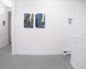 A photograph of 3 images on one wall centrally, and a hallway at left that hosts 1 works