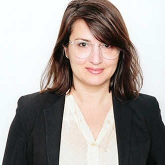 The torso of a woman with medium fair skin, dark hair and brown eyes looks directly at us on a white background. She is wearing clear geometric glasses and a white blouse with a black blazer.