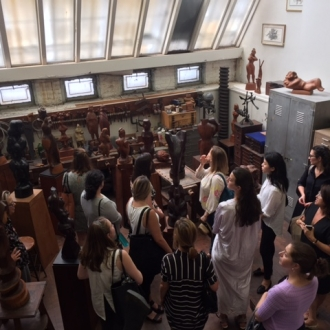 A large group of people crowds into the Chaim Gross Studio. They are surrounded by sculptures in various shades of wood and a large white skylight is above them.