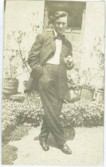 A black and white photograph of a man in a dress suit with a bowtie standing with legs crossed in front of a home with shrubbery and potted plants.