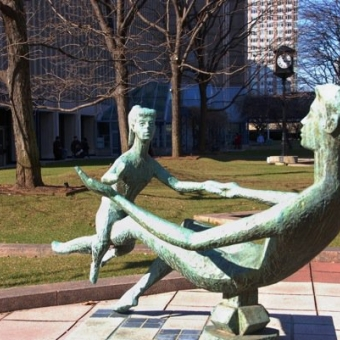 Green bronze sculpture in a park. The sculpture depicts a mother and child facing each other and playing.