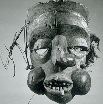 Mask, Ibibio. Mask made of wood, stain, reed, and fabric, replicating a human profile, with eyes carved out beneath the eyelids. The mouth is open, bearing teeth, and its bulbous cheeks and twisted nose greatly protrude from the mask.