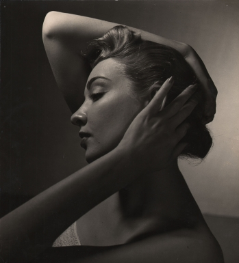 Louise Dahl-Wolfe, Untitled (N.W. Ayer), ​c. 1940. A model in profile, looking left, with hands on her head. One elbow is raised above her head, the other falls below.