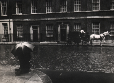David Newell Smith, The man in Downing Street was praying for Mr. Wilson who had just become the Prime Minister, ​c. 1966. A figure with an umbrella kneels on the lower left of the frame across the street from a horse-drawn carriage.