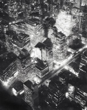 Berenice Abbott, Nightview, New York, ​c. 1932. Aerial, high-contrast night scene encompassing a few city blocks with buildings lit from inside.