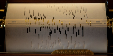 close-up view of player piano roll scrolling through a player piano