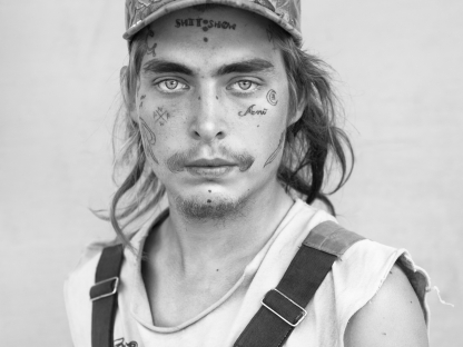 Man with face tattoo and hat by Michael Joseph