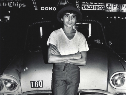 Boy leaning against taxi by Arlene Gottfried