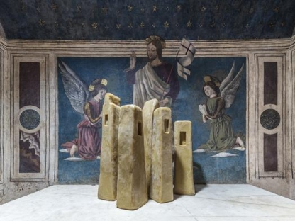 wax tower sculptures in front of frescoes depicting Christ and two angels