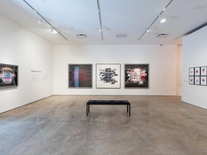 three red and black paintings of seating charts hung in gallery space