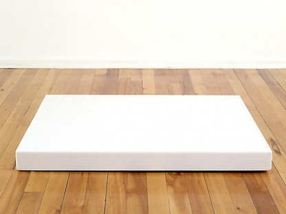 Large white block on a wooden floor