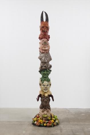 Monster Totem, 2016, Halloween masks, glass eyes, expanding foam, resin, magi-sculpt, fake fruit coated in resin, polyurethane horns, acrylic paint, metal base, wooden pole