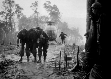 Hugh Van Es- A Wounded Paratrooper of the 101st Airborne Division is Helped Through a Blinding Rainstorm