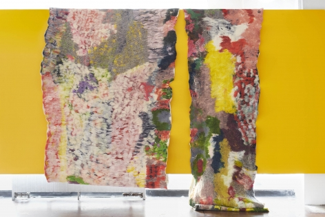 two large multi-colored felt panels lay on top of a yellow wall in the gallery.