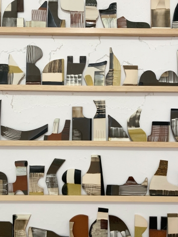 a detail of Katy Fischer's site-specific installation featuring several ceramic tiles of various shapes on wood shelves vertically stacked on one another.