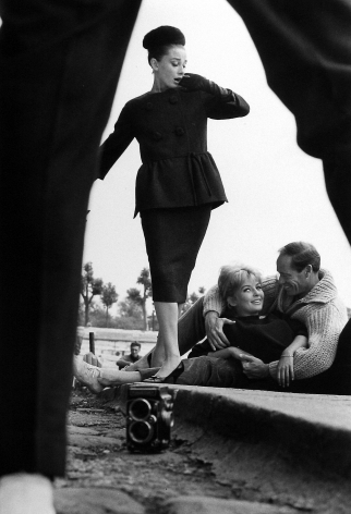 Henry Wolf - Audrey Hepburn view through legs with couple, c.1959 - Howard Greenberg Gallery
