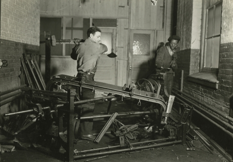 Lewis hine, Scrap metal junkies breaking up old looms, to be sold for scrap iron and said to be sent to Japan for munitions, Paterson, New Jersey, 1936   Gelatin silver print; printed c.1936   4 5/8 x 6 5/8 inches