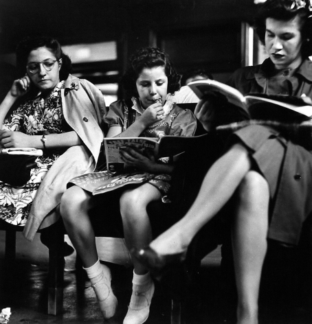 Three women seated on bench in waiting room, 1943