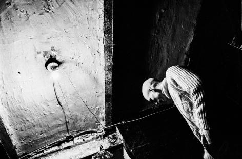 Ken Schles - Craig In Basement With Bare Lightbulb, 1984 - Howard Greenberg Gallery