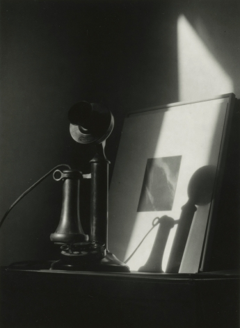 """Dorothy Norman - Telephone, in front of Alfred Stieglitz """"Equivalent,"""" at An American Place, New York, c. 1940 - Howard Greenberg Gallery"""