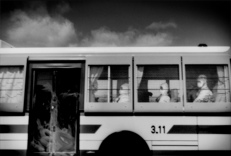 James Whitlow Delano, Black Tsunami, Recovery workers, probably police, wearing hazmat suits to protect them from radiation, enter 20 km no-entry zone via bus, Route 6, Minamisōma, Fukushima Prefecture, Japan, 2011, Sous Les Etoiles Gallery