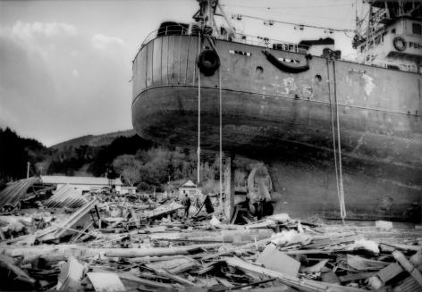James Whitlow Delano, Black Tsunami, An ocean going ship sits where it came to rest in the debris of the great Tsunami that hit, Kesennuma, Miyagi Prefecture, Japan, 2011, Sous Les Etoiles Gallery