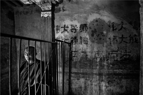 Laurent Zylberman, A Journey in Tibet, A monk near a slogan to the Glory of Mao Zedong at Drepung Monastery, 2008, Sous Les Etoiles Gallery