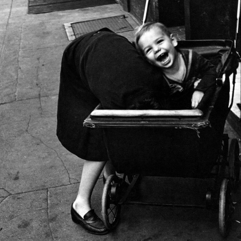 Helen Levitt, New York 1945, child in baby carriage laughs as woman sticks her head inside carriage.