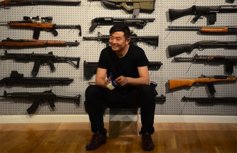 "Complex Magazine: Liu Bolin Performs ""Gun Rack"" At Eli Klein Fine Art in New York"