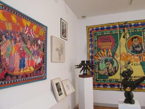"""Two white gallery walls intersect to the left of us. On the right wall a colorful tapestry is hanging, and on the left the vibrant composition by Mimi Gross, """"Fred Dean's Circus in Maine"""" is hung up closest to us. Between those two pieces there are four small art works hung in three cream frames and one black frame. A small dark brown sculpture of four female figures, by Chaim Gross, """"The Flying Ballerinas"""" sits in the middle of the two walls and a small, dark brown sculpture of a person standing on a horse is in the bottom right of the frame, in front of the other pieces."""