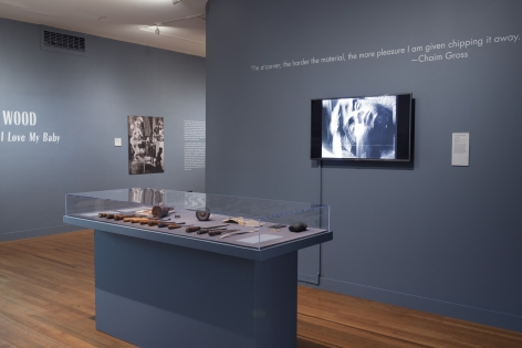 Photo of the exhibit, featuring selected work tools encased in glass, as well as a mounted tv playing a video on Chaim Gross' work. Also on the walls are quotes from Chaim Gross, a black and white photograph of Chaim in his studio, and the title of the exhibit, all in white against the faded navy walls.