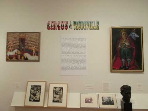 """White gallery wall with large printed description beneath a decorative title """"Circus & Vaudeville"""" in colorful, vintage type. On the left of the description is a large painting with performers and an audience in a medium brown frame, and to the right is painting of man wearing a crown and a red cape in a beige frame with a gold outside. On a small shelf beneath the paintings and description there are two smaller artworks in beige frames on the left, and two photos in black frames and a black bust of a man's head on the right."""